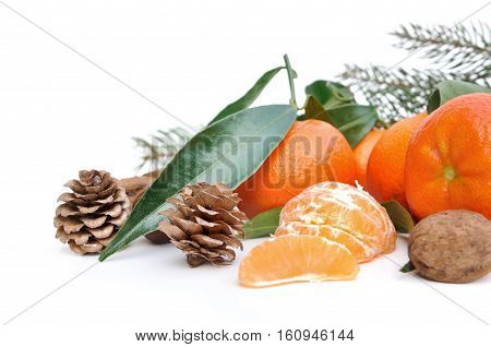 clementines with leaf and pine cones on white background