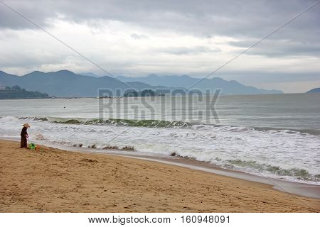 the beach and sea in Nha Trang, sea with waves, choppy, greenish, yellow sand, lots of hills on the horizon, the cloudy sky, on the shore stands a man in a hat Vietnamese