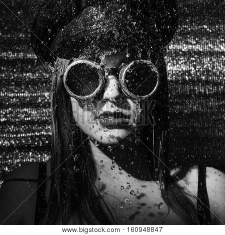 strong girl with glasses and cap standing in the shower. black and white photo