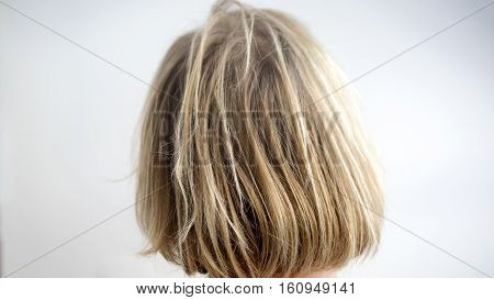 closeup of back of head with uncombed long blond hair