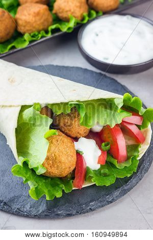 Chickpea falafel balls with vegetables and sauce roll sandwich preparation vertical