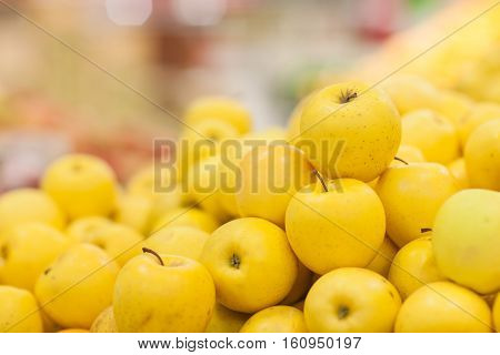 Yellow apples on the shelf in the supermarket