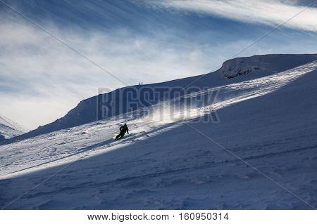 Freeride ski in deep powder snow of Carpathian mountains. Skier skiing downhill in winter mountains.