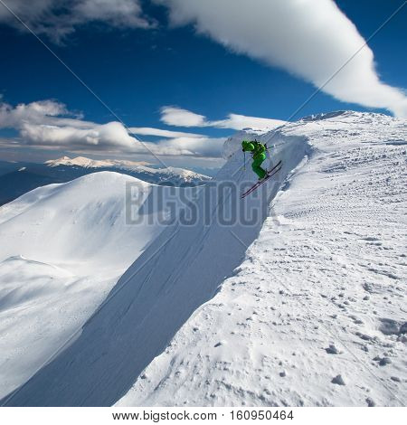 Freeride skier drops off mountain. Extreme skiing in Carpathian mountains in deep powder snow. Hoverla peak on background.