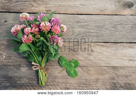 Clovers bouquet and a shamrock on wooden background