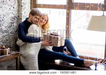 Happy Couple Of Lovers In Pullovers Give Each Other Gifts Sitting