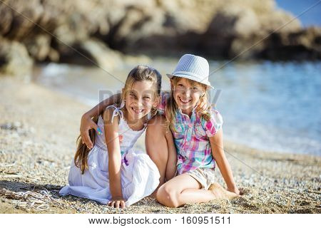 Happy young girls sitting on the beach and laughing