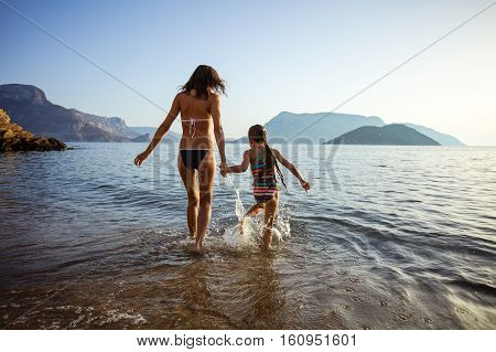 Young woman and her daughter walking in shallow sea waters, girl splashing around