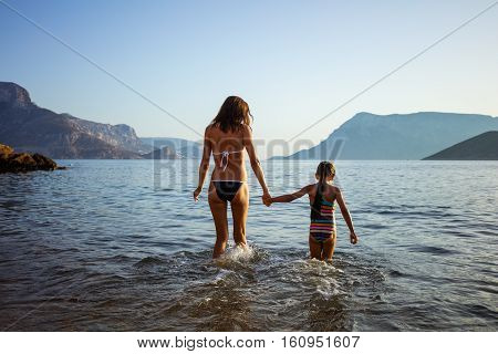 Young woman and her daughter walking in shallow sea waters
