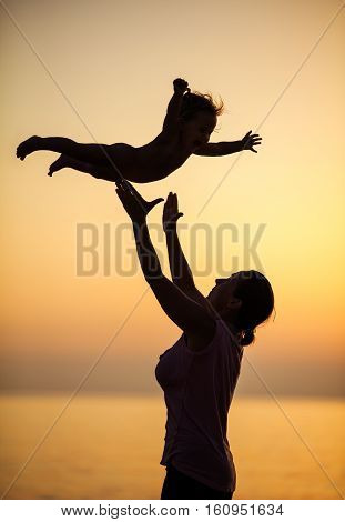 Mother and little daughter having fun on beach at sunset
