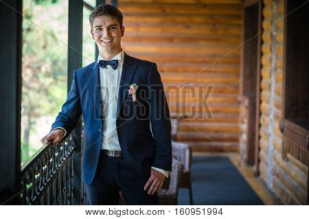 Handsome young bridegroom standing by window and smiling