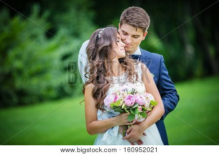 Beautiful young bride and groom in summer park