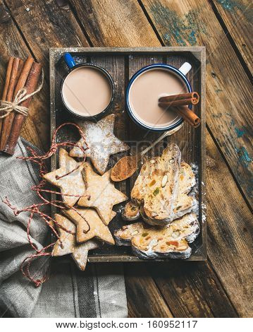 Cocoa in mugs with Christmas gingerbread star shaped cookies, pieces of Stollen cake and spices in wooden tray over rustic wooden background, top view, vertical composition