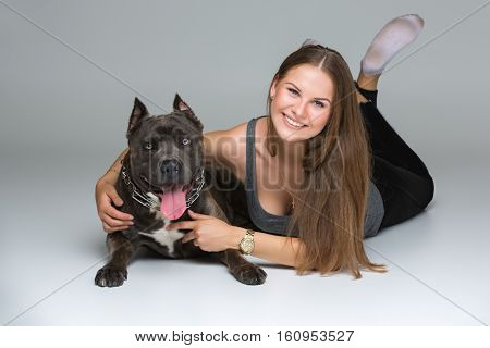 Beautiful sporty young woman lying on floor and hugging adult grey amstafford terrier dog. Studio shot over gray background. Copy space.
