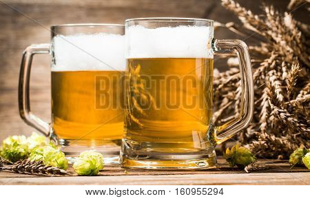 Two foam beer mugs close-up on wooden table