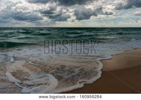 A wavy ocean water surface under cloudy sky.
