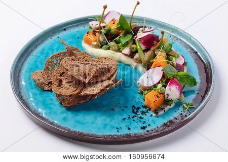 Modern vinaigrette with capers bread crisps pumpkin and pear