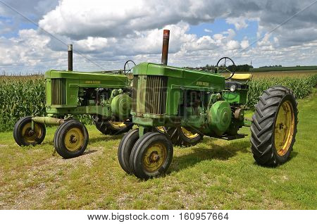 ULEN, MINNESOTA, July 27, 2016:The two old 70 John Deere tractors are products of John Deere Co, an American corporation that manufactures agricultural, construction, forestry machinery, diesel engines, and drivetrains.