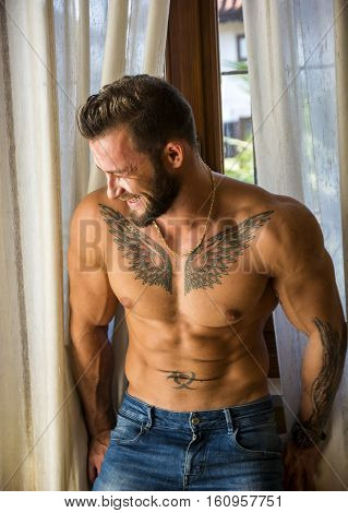 Portrait of sexy shirtless muscular man laughing next to window curtains during the day, wearing only jeans