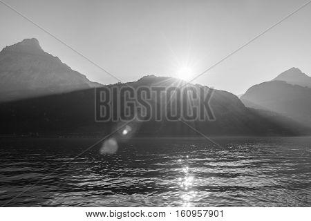 Inspiring panorama of the mountains and lake. The sun sets with bright rays of the tops sun flair. Black and white