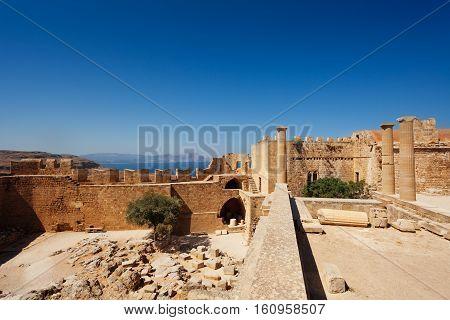 Ancient temple ruins of Lindos Acropolis against blue sky, Rhodes, Greece