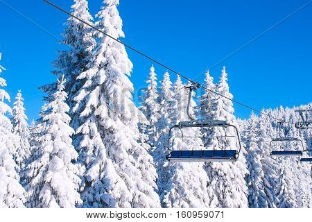 Ski resort image with empty chair lift, blue sky and white snowy pine trees at winter sunny day
