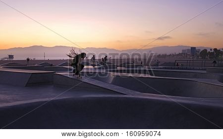 Sunset shot of skater with rasta dread locks up in the air in skate park in California.