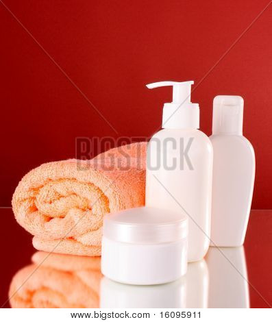 bottles of health and beauty products on red background