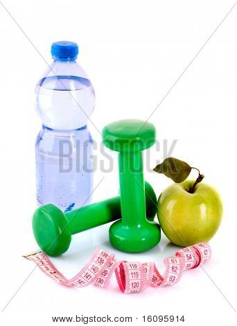 Blue bottle of water, apple and exercise equipment isolated against a white background