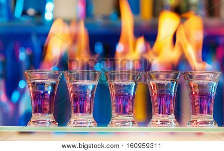 Five shot glasses with flaming cocktails standing in a row on a bar counter