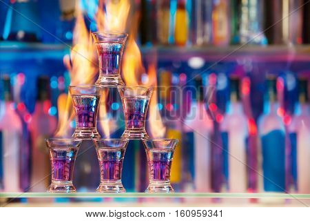 Five shot glasses with flaming cocktails standing in pyramid on bar counter