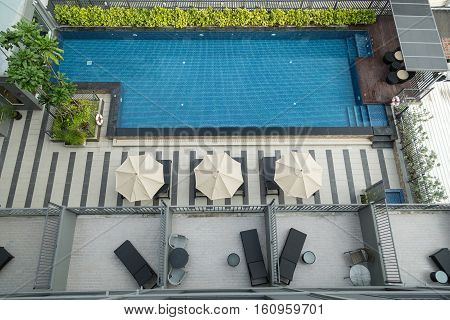 Top view of a condo swimming pool with two empty white deckchairs. poster