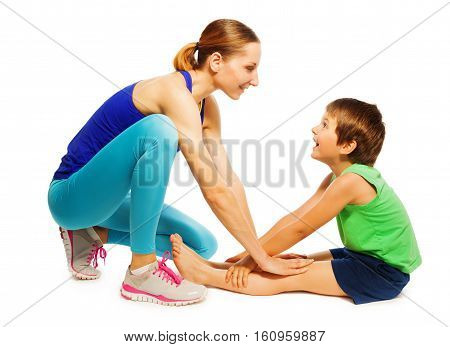 Female trainer teaching happy kid boy stretching leg muscles of back to warm up before training, isolated on white
