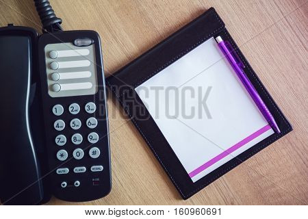 Top ball point pen on notebook with phone .