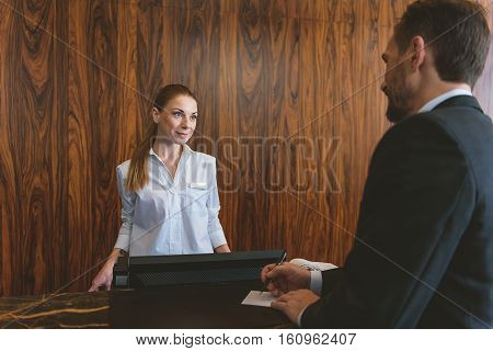 Have pleasant stay. Mature guest paying with check during registration in hotel