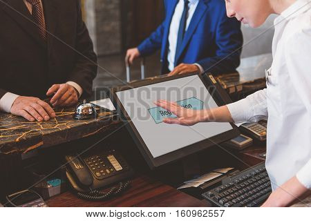 Easy to check in. Female receptionist making registration of two guests and using touch screen