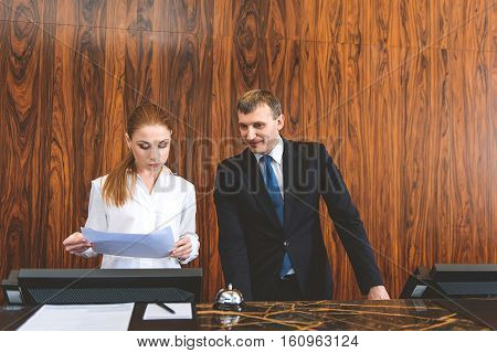 Studying all details. Two professional receptionists standing behind counter and reading documents carefully, holding in their hands