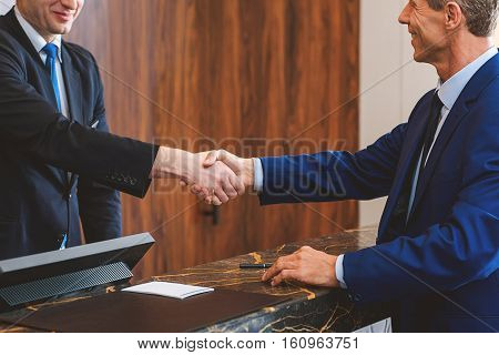 Welcome to apartments. Smiling male receptionist standing behind counter and giving handshake to senior guest