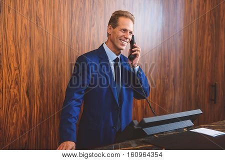 Always ready to help. Smiling adult hotel owner speaking on phone with client while standing behind reception desk