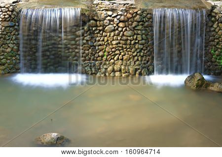 Two small waterfalls separated by a stone wall.