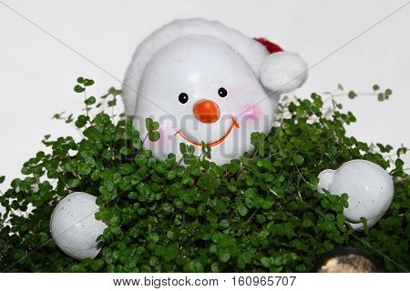A snowman sitting in a green plant pot.