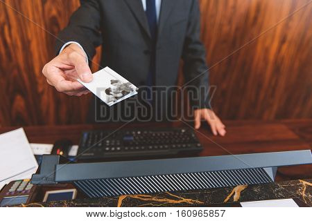 Here is a key. Close up of male receptionist giving cardkey to customer while standing at reception
