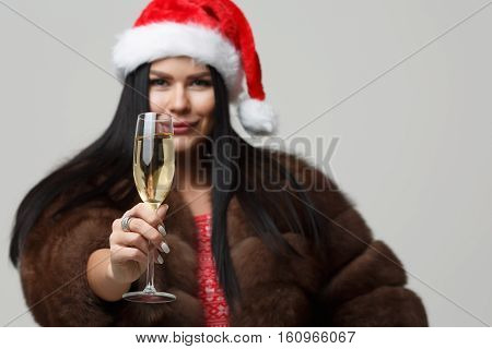 Woman in mink fur coat isolated on gray background with glass of champagne in hand