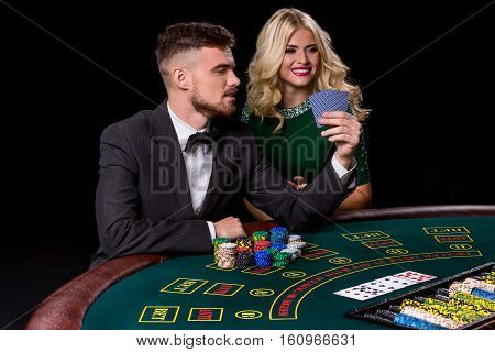 couple playing poker at the green table. The blonde girl and a guy in a suit.