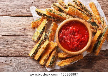 Fried Slices Of Zucchini With Parmesan Cheese And Breading And Tomato Sauce Closeup On A Table. Hori