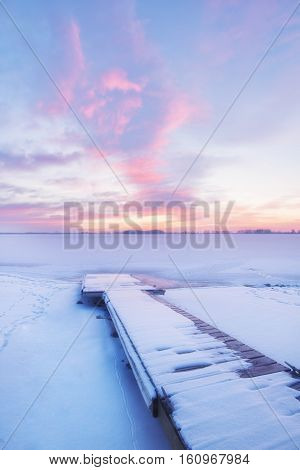 Snow and ice cover a fishing dock as clouds turn pink at sunrise at Lone Tree Reservoir in Loveland Colorado located in Larimer County