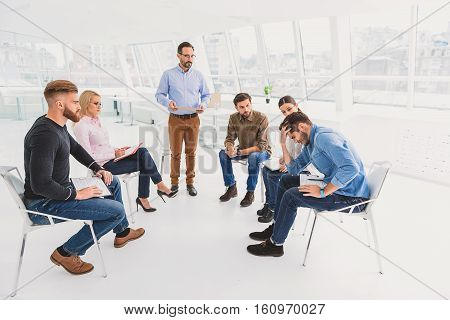 Group of people are sitting and seeing hopeless person with grimace on his face. Serious consultor is standing there