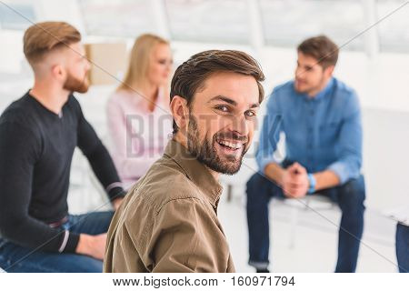 Smiling visitor is sitting among his friends. He looking at camera with interest