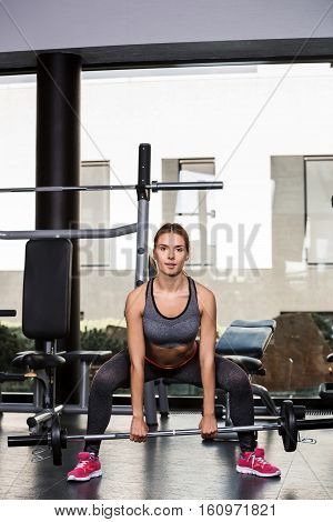 Athletic young woman doing exercises with barbell in the gym. Fitness model working out in a gym. Pretty young woman training to stay fit and healthy