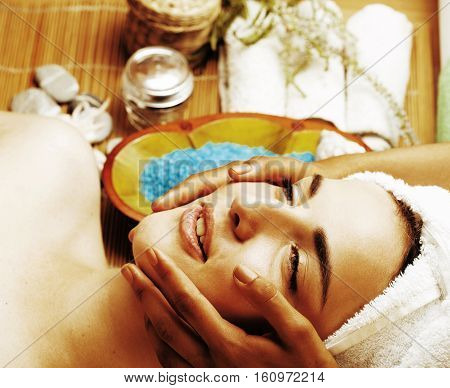 stock photo attractive lady getting spa treatment in salon, close up asian tan hands on face lifestyle